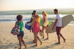Group of friends walking together on the beach on a sunny day. Side view of young group of diverse friends walking together on the beach on a sunny day royalty free stock images