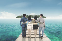 Group of friends walking toward island. Rear view of four friends walking on the wooden jetty toward tropical island while embracing to each other Stock Image