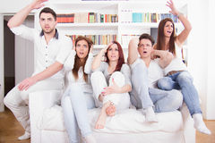 Group of friends watching bad game on tv with expression Stock Photography