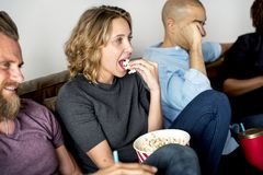Group of friends watching movie. Together and sharing popcorn stock images