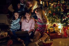Group of friends watching movie on laptop on Christmas eve. Group of happy friends watching movie on laptop on Christmas eve stock photo