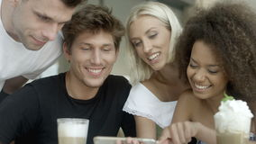 Group of friends watching photos on phone and laughing.
