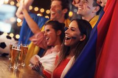 Group of friends watching soccer in pub. Group of friends watching soccer game in pub Stock Photo