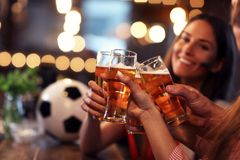 Group of friends watching soccer in pub. Group of friends watching soccer game in pub Royalty Free Stock Photos