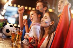 Group of friends watching soccer in pub. Group of friends watching soccer game in pub Royalty Free Stock Photography