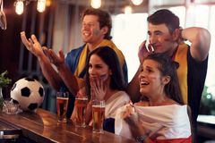 Group of friends watching soccer in pub. Group of friends watching soccer game in pub Stock Images