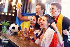 Group of friends watching soccer in pub. Group of friends watching soccer game in pub Stock Photography