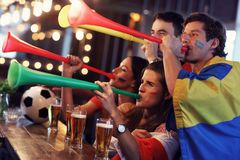 Group of friends watching soccer in pub. Group of friends watching soccer game in pub Royalty Free Stock Image