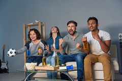 Group of friends watching sport together. So strong emotions. Four football fans rooting for their soccer team on TV and sitting on white sofa at home Royalty Free Stock Images