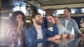Group of friends watching sports program in bar, upset about losing game, defeat royalty free stock photography