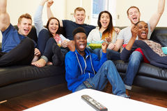Group Of Friends Watching Television At Home Together. Sitting Down Cheering Royalty Free Stock Photos