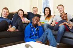 Group Of Friends Watching Television At Home Together. Sitting Down Smiling Royalty Free Stock Images