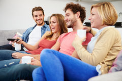 Group Of Friends Watching Television Together At Home Stock Photo