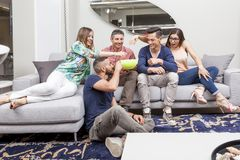 Group of friends watching tv and eating popcorn on sofa Royalty Free Stock Photo