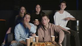 Group of friends watching on the TV a football match they support their favorite team while drinking some beer and