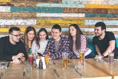 Group of friends watching videos on smartphone at pub restaurant