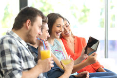 Group of friends watching videos in a tablet royalty free stock photos