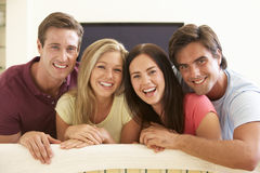 Group Of Friends Watching Widescreen TV At Home Stock Photo