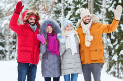 Group of friends waving hands in winter forest Royalty Free Stock Image