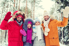 Group of friends waving hands in winter forest Stock Image
