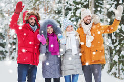Group of friends waving hands in winter forest Stock Photos