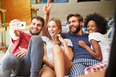 Group Of Friends Wearing Pajamas Taking Selfie On Mobile Royalty Free Stock Photography