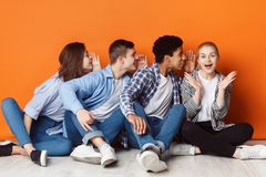 Group of friends whispering each other in the ear. Over orange background royalty free stock photos