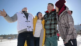 Group of Friends During Winter Holidays on Blue Sky Background. Men and Women are Enjoying Warm Winter Weather Being in stock video footage