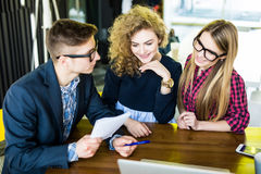 Group of friends working on their small business modern office. Man show on his notice on notebook. Group of friends working on their small business at modern royalty free stock image