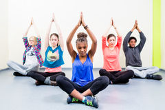 Group for friends in yoga class meditating Stock Photos