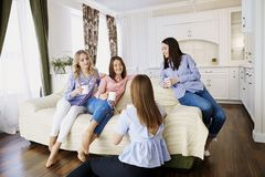 A group of friends of young girls talk at a meeting in a room. A group of friends of young girls talk at a meeting in a room indoors royalty free stock photos