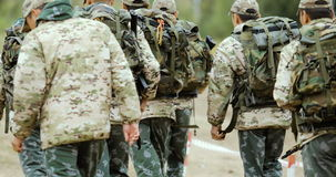 Group of Fully Equipped and Armed Soldiers Walking Forward Outwards Camera in Desert Environment. stock footage