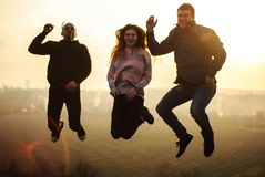 Millennials jump friends in the outdoors at evening spring sunset royalty free stock photos