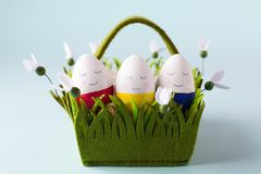 A group of funny colorful eggs in a basket - a concept of merry Easter, funny characters, emotions. stock photos