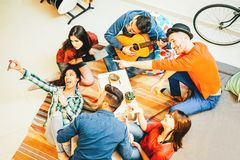 Group of funny friends enjoying together playing music with guitar and taking selfie with mobile phone stock image
