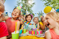 Group of funny kids having fun around party cake Stock Photos