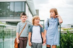 Group of three funny kids wearing backpacks walking back to school Royalty Free Stock Photos