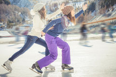 Group funny teenagers ice skating outdoor at ice rink Stock Images