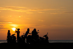 Group Gang of Teenagers Young Adults watch a beach side sun set. On their scooters stock photo