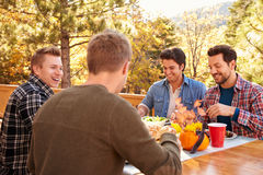 Group Of Gay Male Friends Enjoying Outdoor Meal Together royalty free stock image