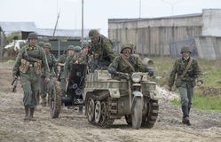 A group of German soldiers with the tractor SdKfz 2, and anti-tank guns moving on the road. Reconstruction of the episode of the Stock Photography