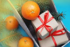 Group of Gift boxes Wrapped in Craft Paper with Satin Ribbon Tangerine and Christmas on blue Background royalty free stock photography