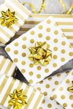 Group of gifts in white and gold paper on a gray background.  Royalty Free Stock Image