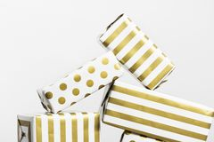 Group of gifts in white and gold paper on a gray background.  Royalty Free Stock Images