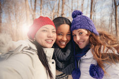 Group of girl friends enjoying taking selfies in the snow in winter. Group of millenial young female adult friends enjoying wintertime and in a snow filled park royalty free stock photography