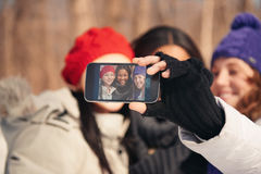 Group of girl friends enjoying taking selfies in the snow in winter. Group of millenial young female adult friends enjoying wintertime and in a snow filled park stock photography
