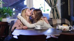 Group of girl friends meeting for coffee and talk. Two beautiful young girlfriends sitting in modern coffee shop and talking with happy smiles while waiting for stock footage