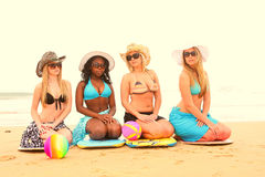 Group of girl friends sitting on their knees Stock Photo