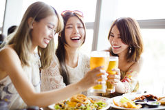 Group of girl friends toasting and eating Stock Image