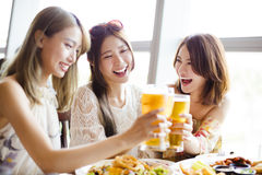 Group of girl friends toasting and eating Royalty Free Stock Images